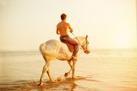 Macho man and horse on the background of sky and water. Boy model, cowboy on horseback on the beach by the sea at sunset. Men, backlit in sunshine. A positive summer time scene.