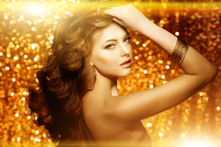 Golden beautiful fashion woman, model with shiny  healthy long volume hair. Waves curls updo volume hairstyle. Hair Salon.Girl with luxurious haircut on  gold background Banque d'images