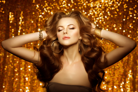 lux: Golden beautiful fashion woman, model with shiny  healthy long volume hair. Waves curls updo volume hairstyle. Hair Salon.Girl with luxurious haircut on  gold background Stock Photo