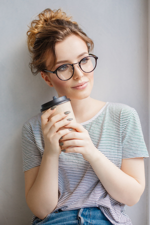 woman on phone: Young trendy woman by the window. A hipster style girl with a phone and coffee in fashion glasses sits alone on a windowsill Stock Photo