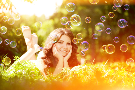 Woman and soap bubbles in park . Positive summertime scene. Happy girl model outdoors Against the background of green grass and trees photo