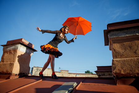 woman on phone: Young beautiful woman on the roof with an umbrella. Romantic walk model girls on the sky background