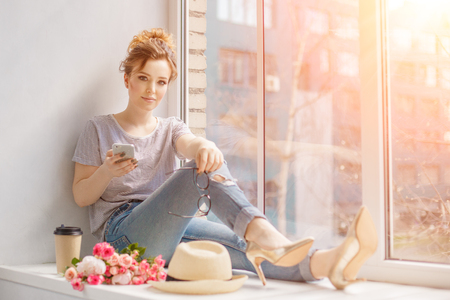 descansando: Young trendy woman by the window. A hipster style girl with a phone and coffee in fashion glasses sits alone on a windowsill Foto de archivo