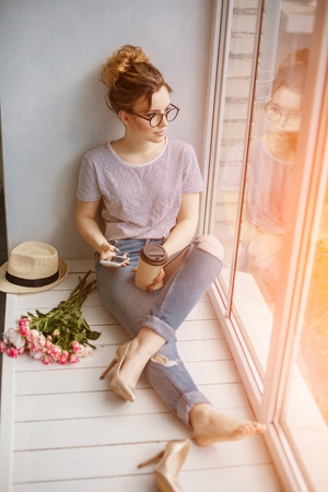 mujeres tristes: Young trendy woman by the window. A hipster style girl with a phone and coffee in fashion glasses sits alone on a windowsill Foto de archivo