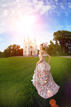 A woman like a princess in an vintage dress before the magic castle photo