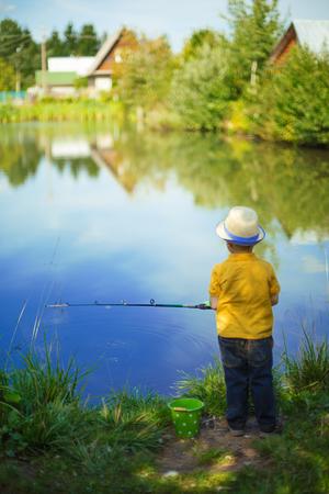 Kleiner Junge nimmt an der Fischerei in einem Teich teil. Kind mit einer Molkerei in seinen Händen.