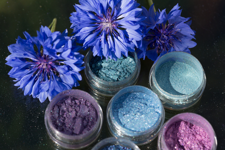 Cosmetics. Pigments for make-up, eyes, lips, face and body. Brilliant radiant, scattered multicolored powders. Stock Photo