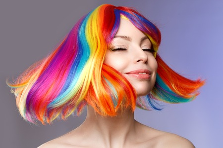 Woman hair as color splash. Rainbow up do short haircut. Beautiful young girl model with glowing  healthy skin. Stock Photo