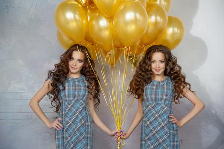 Updo の髪を持つ女の子双子の姉妹は、金色の風船や星の背景を partyon ています。誕生日パーティーの女性たち