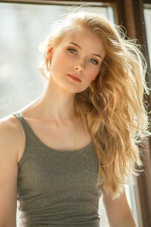 Romantisch blondje. Jonge mooie leuke vrouw. Schoonheidsmeisje met lang glanzend haar, gloeiende huid en omvangrijk kapsel Stockfoto