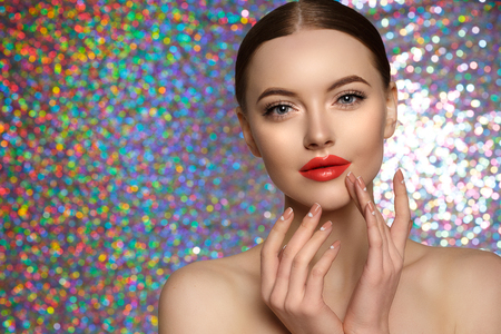 Young Beauty Woman touch own face. Fresh clean fresh glowing Skin. Beautiful girl with perfect makeup, bright manicure. Cosmetology and Facial Treatment, spa. Stock Photo