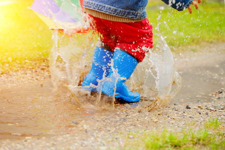 Child jumps on puddles in boots. Baby in the rain. A boy with a rainbow umbrella is walking outside. Autumn, vacation Stock Photo