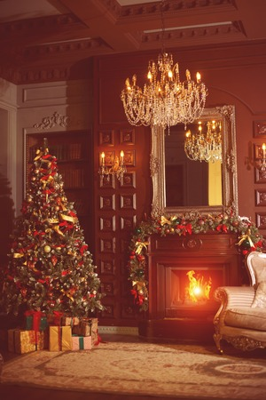New Year's luxurious interior with Christmas tree spruce, fire in the fireplace and gifts.
