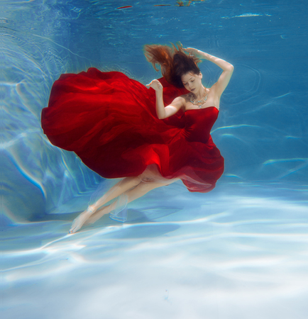 Girl mermaid. Underwater scene. A woman, a fashion model in the water in a beautiful dress swims like a fish. 写真素材