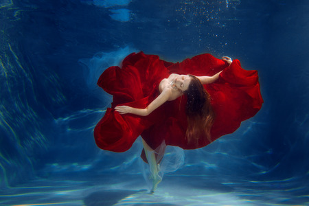 Girl mermaid. Underwater scene. A woman, a fashion model in the water in a beautiful dress swims like a fish. 版權商用圖片