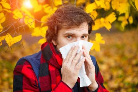 Man with cold rhinitis on autumn background. Fall flu season. Ill sick sneezing male. Handkerchief, vaccine against influenza virus Caught Cold Headache Allergy runny nose