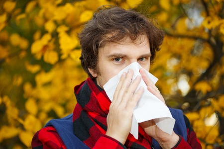 Man with cold rhinitis on autumn background. Fall flu season. Ill sick sneezing male. Handkerchief, vaccine against influenza virus Caught Cold Headache Allergy runny nose