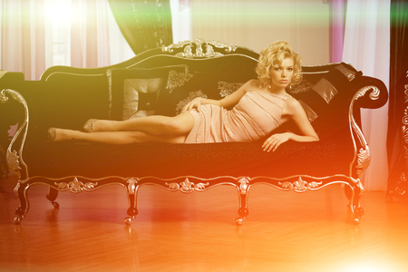 Beauty young model woman in luxurious evening dress in a fairy luxury apartment. Beautiful makeup and hairstyle. Classic vintage home interior. Light rays of a nightclub. Reklamní fotografie