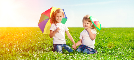 Two little girls together in outdoor park  at sunny day. Sisters in the green garden. Stok Fotoğraf