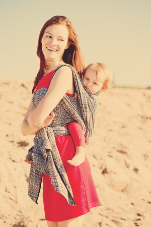 Beautiful woman with a baby in a sling. Mom and baby. Mother and child Stockfoto