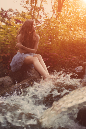 Beautiful woman in fairy forest near a stream. Girl model in the forest, among the grass and leaves near the water.