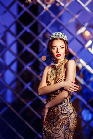 Woman queen princess in crown and lux dress, lights party background Luxury girl Long shiny healthy volume hair Waves Curls Updo Hairstyle. Salon Fashion model luxurious vintage interior Jewelry Earri