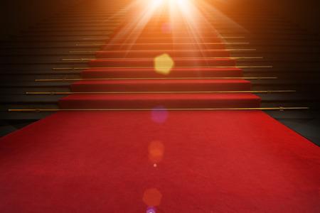 Rode loper op de trap op een donkere achtergrond. Het pad naar glorie, overwinning en succes Stockfoto