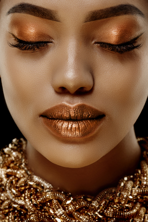 Gold Luxury black skin woman African Ethnic female face. Young african american model with jewelry Stockfoto