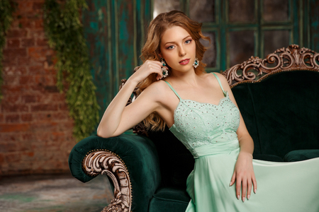 Luxury woman model in a mint-colored dress sitting on a vintage couch. Beauty girl with a stunning makeup and hairstyle. Banco de Imagens