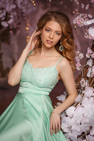 Beautiful woman model in a mint-colored dress on a flowered spring background. Beauty girl with a stunning makeup and hairstyle. Banco de Imagens