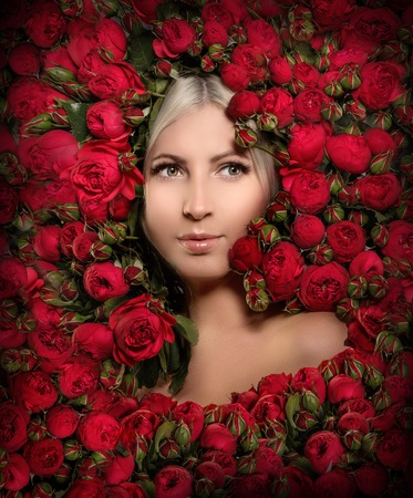 Beautiful woman in a frame of flowers. Young girl with red peony roses.