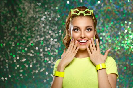 Trendy girl with bright green neon accessories. Model in a disco nightclub. Woman at a theme party in the rays of light.