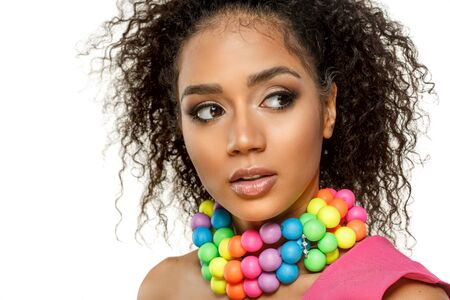 Beauty black skin woman fashion african ethnic female face portrait. Young girl model with afro and extraordinary brightly colored rainbow beads around the neck