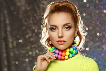 Rainbow girl. Model with colorful bright jewelry. Woman with neat makeup and high hairstyle with colored necklace and earrings.
