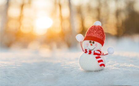 Snowman in winter wonderland scene. Christmas, New Year postcard design. Wintertime magic. Snowman in december snow at sunset Reklamní fotografie