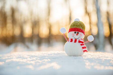 Snowman in winter wonderland scene. Christmas, New Year postcard design. Wintertime magic. Snowman in december snow at sunset