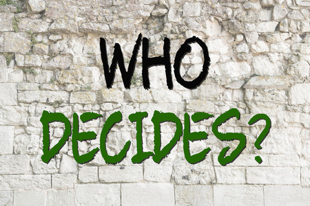 decission: Text who decides concept on a old wall as background