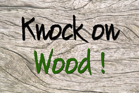 saying: Text knock on Wood saying on a wooden background