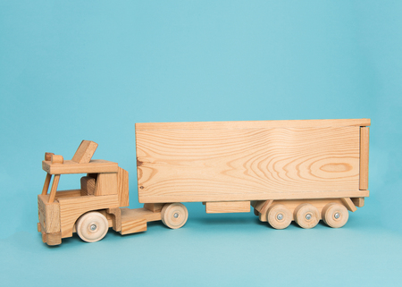 birth announcement: Wooden toy truck on a blue background with space for text as a birth announcement card or birthday card