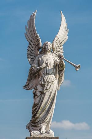 Cimitero statua bianca araldo angelo su un cielo blu con nuvole bianche