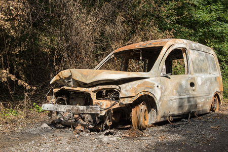 Old burned out car on an abandoned road Stock Photo