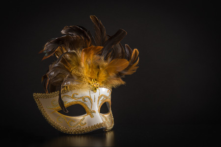 Pretty venician golden carnival mask with feathers isolated on a mysterious black background