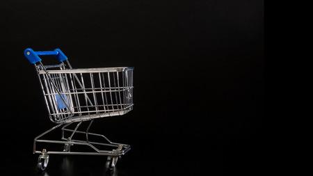 empty shopping cart: Empty shopping cart on a black background Stock Photo