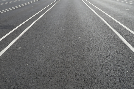 White line on a black asphalt street directing to one point Stock Photo