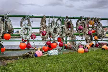 Landscape of a harbor with fishermans equipment with orange buoy, rope and nets hanging over a gate Stock Photo