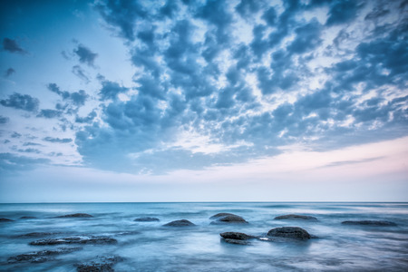 Landscape with blue skye, clouds and stones in the sea