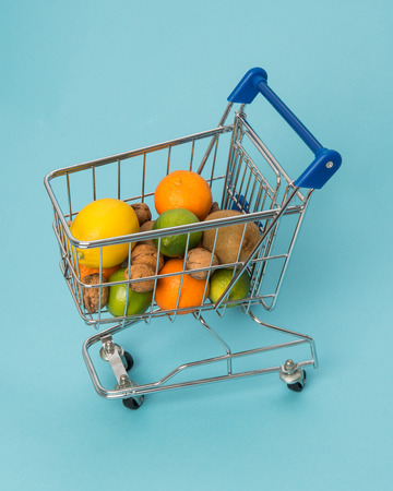 Shopping cart seen from above with fruits on a blue background Stock Photo