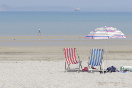 Beach in Engeland Weymout with chairs and a Beach umbrella, birds, tanker boat, and two persons in the sea