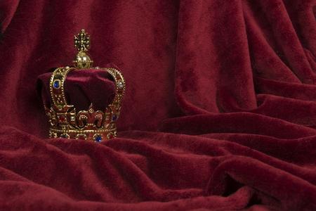 Golden crown on a red velvet background