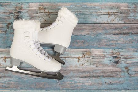 White ice skated for women on a blue wooden background Stock Photo